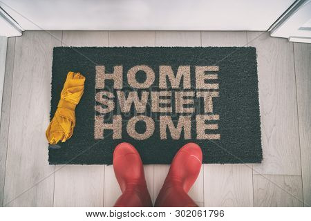 Rain boots selfie walking on doormat entrance welcome sign saying Home Sweet Home with yellow umbrella for autumn real estate moving in concept.