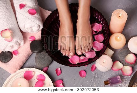 Woman soaking her feet in bowl with water and rose petals on floor, top view. Spa treatment poster