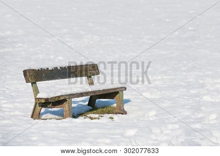 Snow Covered Park Bench On A Sunny Winter Day