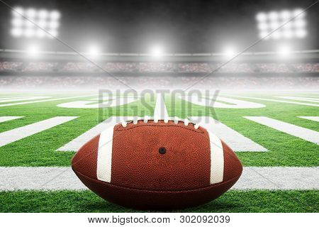 Close Up Of American Football On Stadium Field With Yard Line Markings And Spotlight With Blurred Ba