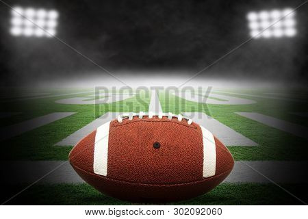Close Up Of American Football On Stadium Field With Yard Line Markings And Dramatic Spotlight With R