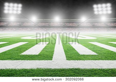 Close Up Of American Football Stadium Field With Yard Line Markings And Spotlight With Blurred Backg