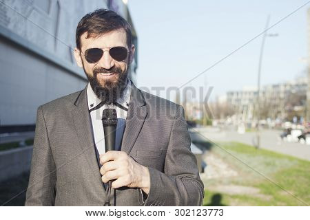 The Journalist Or Anchorman Or Tv Reporter Is Outdoors On The Street In Live Program.