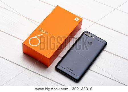 Kharkiv, Ukraine - 02 Fabruary 2019: New Xiaomi Redmi 6 smartpphone on a wooden table