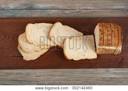 Many Mixed Breads And Rolls Of Baked Bread On Wooden Table Background. Top View