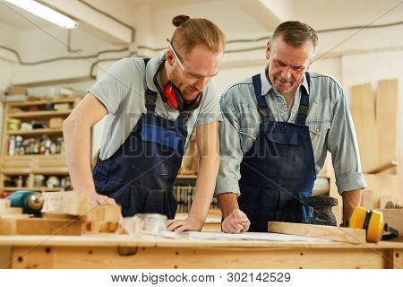 Waist up  portrait of senior carpenter teaching apprentice  while working together  in joinery workshop poster