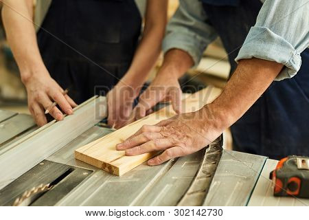 Close Up Of Senior Carpenter Working With Apprentice In Joinery Workshop, Copy Space
