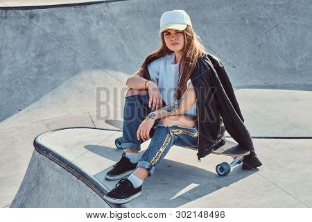 Young Attrctive Girl Is Sitting On Her Longboard At Skatepark. She Is Wearing Denim, T-shirt, Jacket