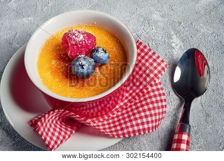 Creme Brulee (cream Brulee, Burnt Cream) With Raspberry And Blueberry, Powdered With Sugar On Rough