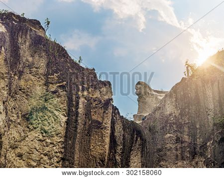 Hard Rock Cliff And Blue Cloudy Sky With Sun Light Flaring From Behind The Cliff
