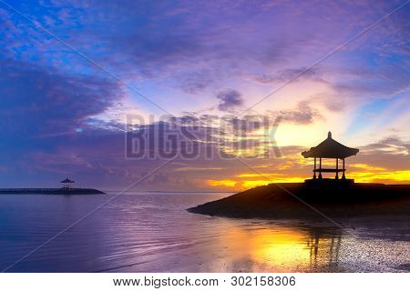 Beachfront Pavilion Silhouette In Sunrise Or Sunset Time. Colorful Blue Yellow Sky With Purple Cloud