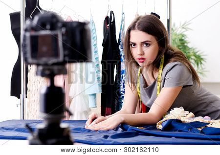 Young beautiful female tailor recording video for her blog