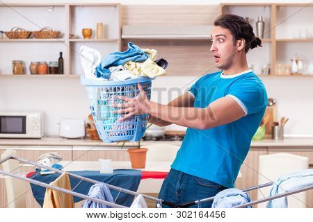 Young man husband doing clothing ironing at home