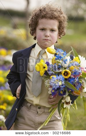 Young boy with angry face holding flowers outdoors