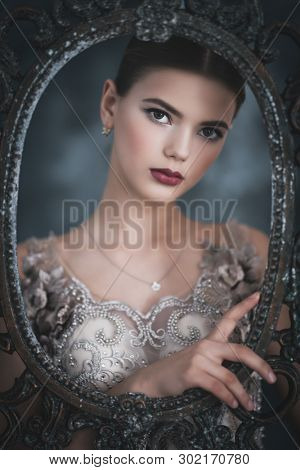 A close up portrait of a dreamy lady in a in embroidered dress posing in the frame of an old mirror.  Wedding, beauty, fashion.