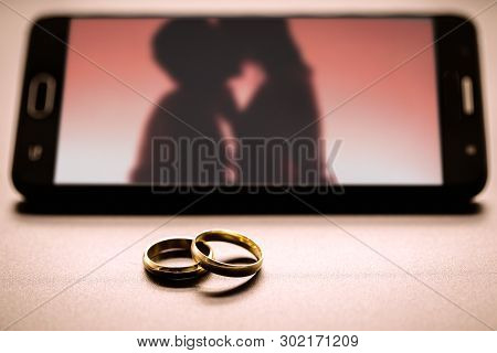 Concept Of Lovers Or Marital Betrayal, Infidelity. Pair Of Rings Next To A Smartphone, With An Image