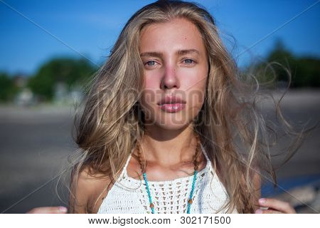 close horizontal portrait of a young blonde with long blown-down hair. serious, calm face poster