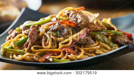 asian stir fried noodles with beef peppers and onions panorama