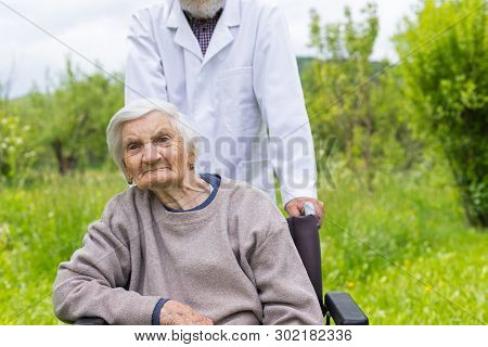 Senior Woman With Dementia Sitting In A Wheelchair Outdoor, Male Doctor Taking Care Of Her - Elderca
