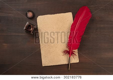 A Vintage Background With A Quill Pen On A Piece Of Old Parchment Paper, With An Ink Well, Shot From