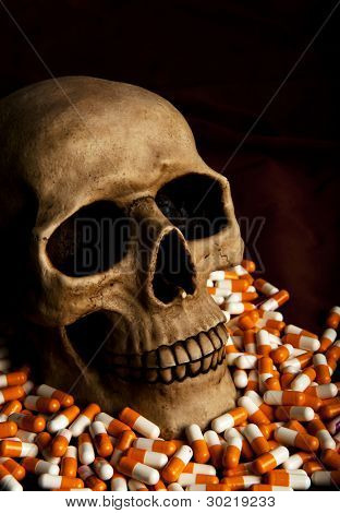 Dramatic skull in the pile of drugs stands for sickness and danger of abuse