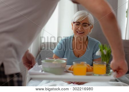 Contended Lady Looking At Breakfast While Lying In The Bed