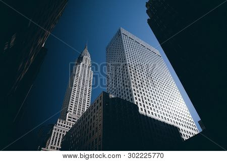 A View Of The Chrysler Building From Street Level Looking Up With Blue Skies. New York City, New Yor