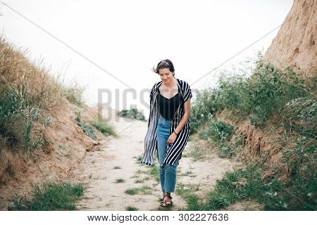 Stylish Hipster Girl Walking  Between Sandy Cliffs With Grass At Sunset. Happy Young Boho Woman Expl