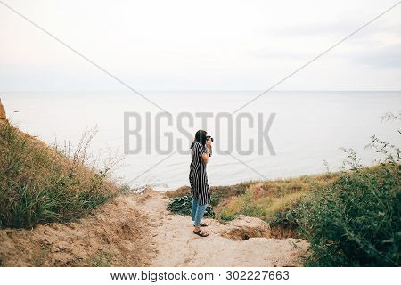Stylish Hipster Girl Relaxing On Sandy Cliff And Holding Photo Camera.  Happy Young Boho Woman Explo