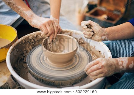 Pottery Workshop. Hands Of Adult And Child Making Pottery, Working With Wet Clay Closeup. Process Of