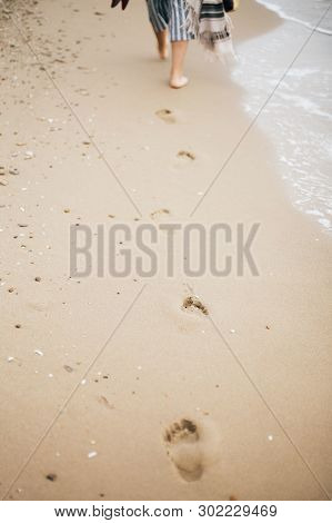 Stylish Hipster Girl Walking Barefoot On Beach, Holding Bag And Shoes In Hand. Footprints On Sand Cl