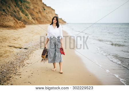 Stylish Hipster Girl Walking Barefoot On Beach, Holding Bag And Shoes In Hand. Happy Boho Woman Rela
