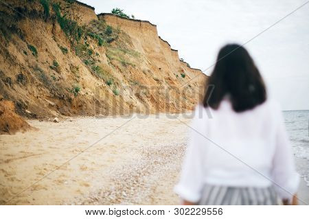 Sand Cliff And Beach Near Sea And Blurred Image Of Hipster Girl Walking And Relaxing. Summer Vacatio
