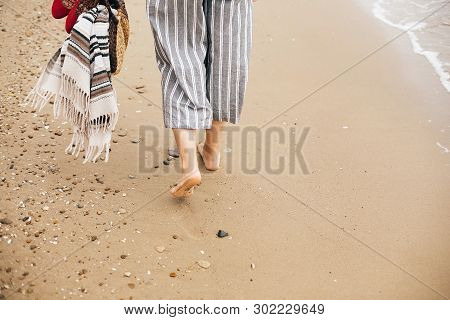 Stylish Hipster Girl Walking Barefoot On Beach, Holding Bag And Shoes In Hand, Closeup. Summer Vacat