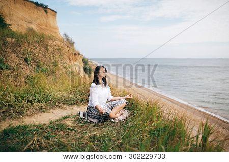 Stylish Hipster Girl Sitting On Beach And Doing Yoga. Happy Boho Woman Practicing Yoga And Meditatio
