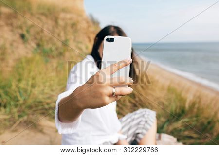 Stylish Hipster Girl Sitting On Beach And Holding Phone, Taking Selfie. Happy Boho Woman Practicing