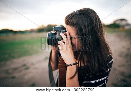 Stylish Hipster Girl Taking Photos On Beach At Sunset. Summer Vacation. Portrait Of  Happy Boho Woma