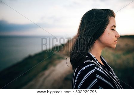 Stylish Hipster Girl Relaxing On Beach At Sunset. Summer Vacation. Portrait Of  Happy Boho Woman Enj