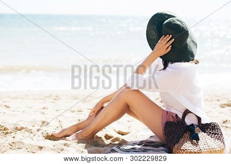 Stylish Hipster Girl In Hat Sitting On Beach With Straw Bag And Tanning Near Sea Waves. Summer Vacat