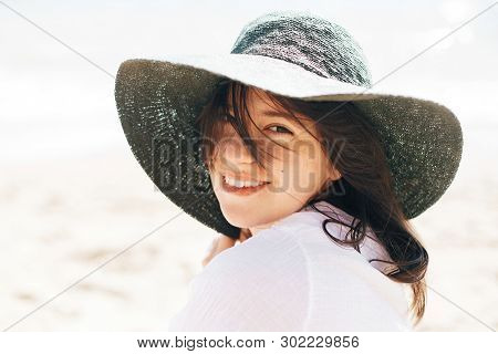 Happy Young Boho Woman In Hat Relaxing And Enjoying Sunny Warm Day At Ocean. Space For Text. Stylish