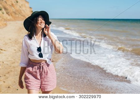 Stylish Hipster Girl In Hat Walking On Beach And Smiling. Summer Vacation. Happy Young Boho Woman Re