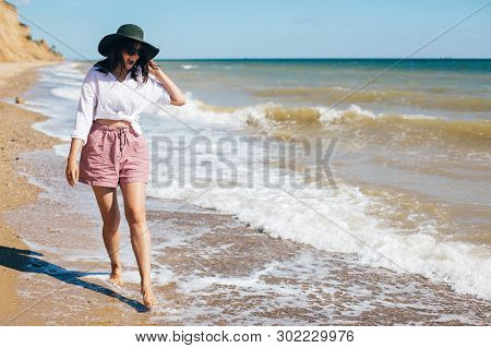 Summer Vacation. Happy Young Boho Woman Walking And Having Fun In Sea Waves In Sunny Warm Day On Tro