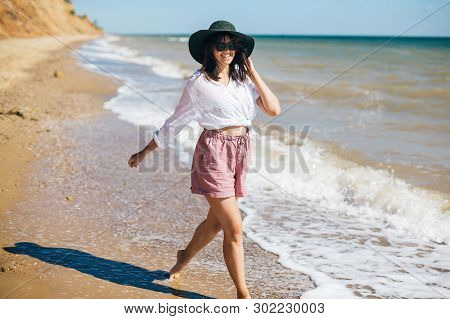 Summer Vacation. Happy Young Boho Woman Walking In Sea Waves In Sunny Warm Day At Tropical Island An