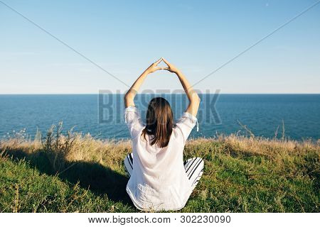 Yoga Day. Stylish Hipster Girl Sitting In Yoga Pose And Relaxing On Mountain With Sea View. Happy Bo