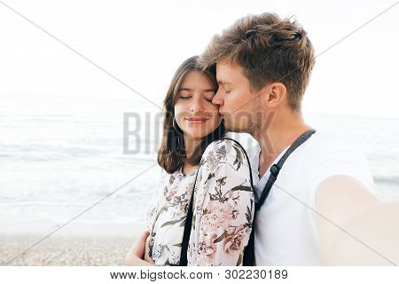 Stylish Hipster Couple Taking Selfie On Beach And Kissing At Evening Sea. Summer Vacation. Portrait