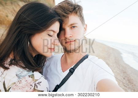 Stylish Hipster Couple Taking Selfie On Beach At Evening Sea. Summer Vacation. Portrait Of Happy You
