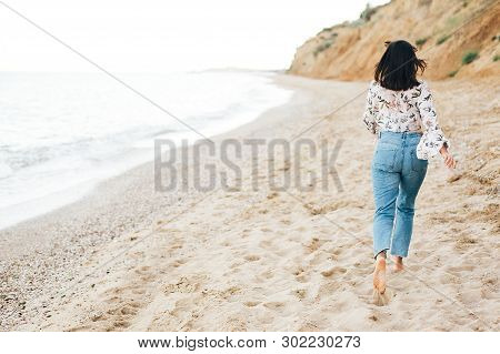 Stylish Hipster Girl Running Barefoot On Beach At Sea , Back View. Happy Fashionable Boho Woman Rela