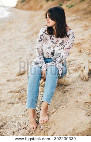 Stylish Hipster Girl Sitting On Beach At Sea. Happy Fashionable Boho Woman In Denim Jeans And Floral