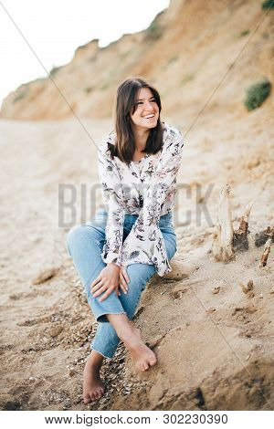 Stylish Hipster Girl Sitting On Beach At Sea And Smiling. Happy Fashionable Boho Woman In Denim Jean