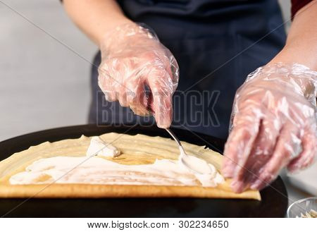 Cropped View Of Chef In Blue Apron In Dish Preparing Process. Woman Hands In One-time Gloves Lubrica